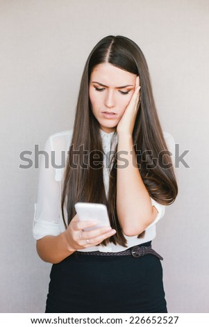 young girl looking in the phone and a frustrated - stock photo