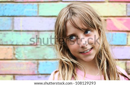 Young girl looking left with colorful brick work as background - stock photo