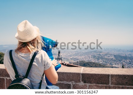 Young girl looking through a coin operated binoculars on the Barcelona - stock photo