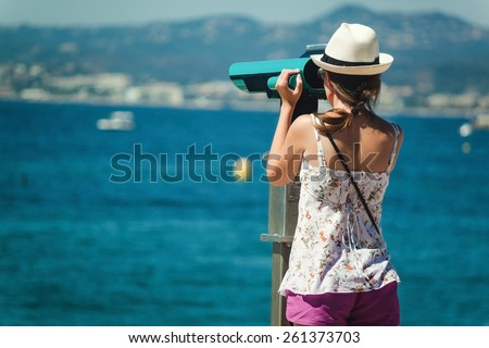 Young girl looking through a coin operated binoculars on the sea shore of Cannes, France. - stock photo