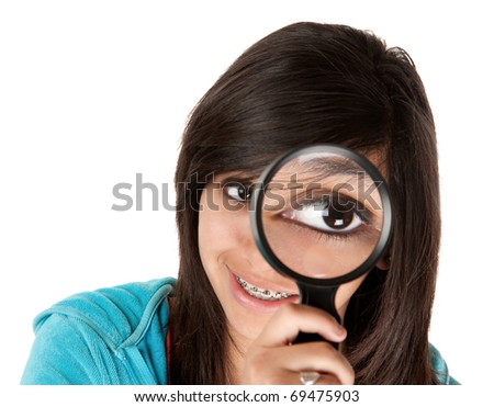 Young girl looking through a magnifying glass - stock photo