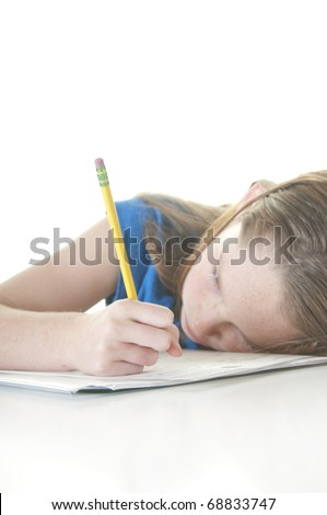 Young girl looking tired with school work - stock photo