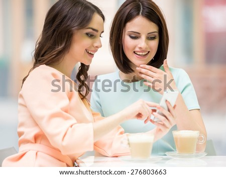 Young girl looking to her friend's phone and feeling exciting while sitting in urban cafe. - stock photo
