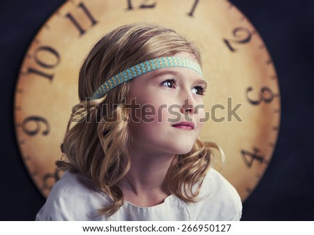 Young girl looking to the side with a large vintage clock behind her - stock photo