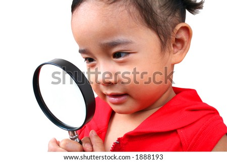 Young girl looking true the magnify glass. - stock photo