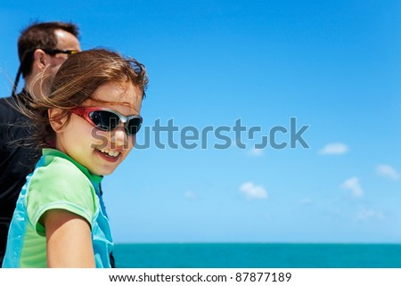 Young girl looks down over the side of a boat - stock photo