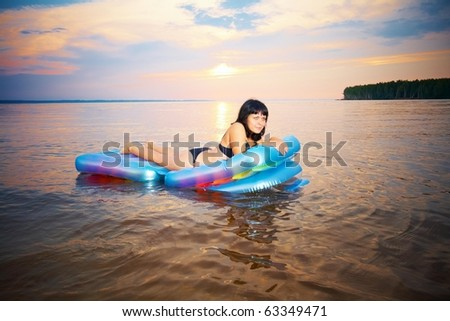 young girl lying down on the airbed - stock photo