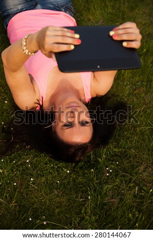 Young girl lying in the grass and working on a tablet. - stock photo