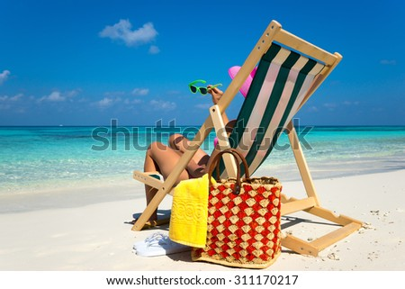 Young girl lying on a beach lounger with glasses in hand on the tropical island - stock photo