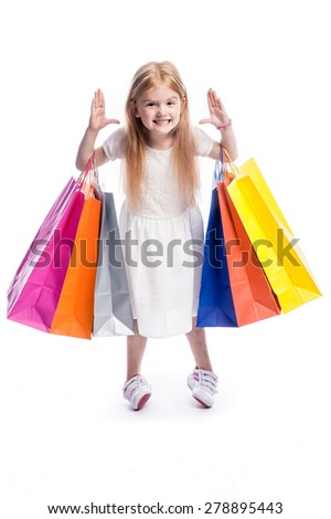 Young girl making a funny face with big shopping bags. - stock photo