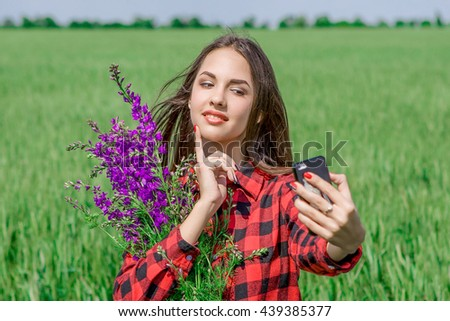 Young girl making selfie. Beautiful young women making selfie and grimacing. In  field with flowers - stock photo