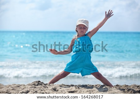 Young girl meditating in yoga pose standing on sandy sea beach - stock photo