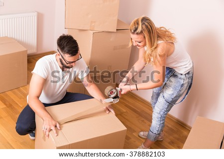 Young girl moving in a new apartment with her boyfriend,standing surrounded with cardboard boxes, packing and taping boxes, while the boyfriend carries boxes away - stock photo