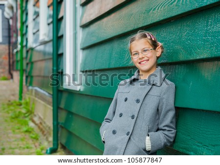 Young girl near green wooden wall looking at the camera - stock photo