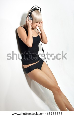 Young girl near white wall listening music - stock photo