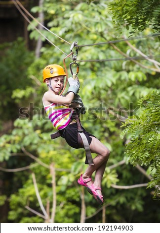 Young girl on a jungle zip line - stock photo
