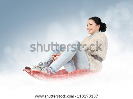 Young girl on a sled in the snow, concept winter games - stock photo