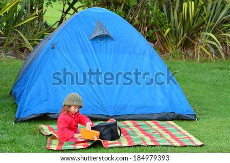 Young girl on camping holiday having a picnic outside a tent outdoor.Concept photo of child , children, camping, outdoor, nature, adventure, holiday. - stock photo
