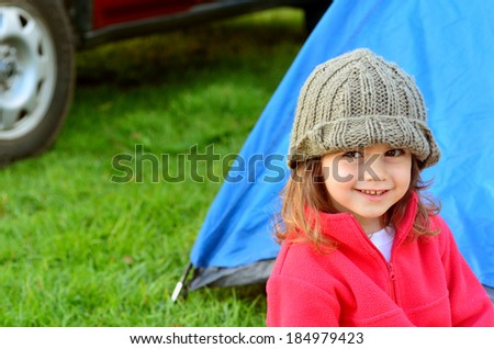 Young girl on camping holiday smiling while looking away from the camera, relaxing outside a tent outdoor. Concept photo of child , children, camping, outdoor, nature, adventure, holiday. - stock photo