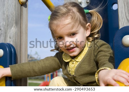 Young girl on slide in playground - stock photo