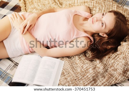 young girl on sofa with book - stock photo