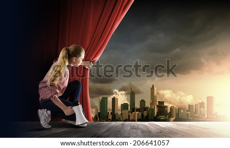 Young girl on stage with megaphone opening red curtain - stock photo