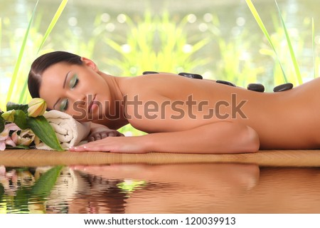 young girl on stone therapy at the spa salon - stock photo