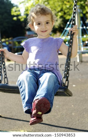 Young girl on swing. A girl, toddler, wearing lilac purple top and blue jeans. She has blonde curly hair and is smiling at camera whilst swinging on a swing at the park/ playground. - stock photo