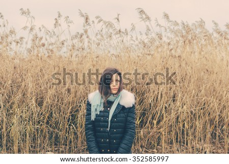 young girl on the lake in autumn time - stock photo