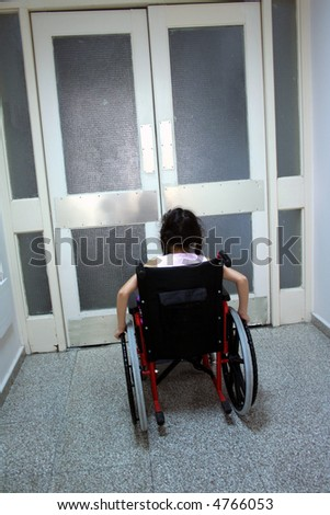 Young girl on wheelchair in front of closed doors - stock photo