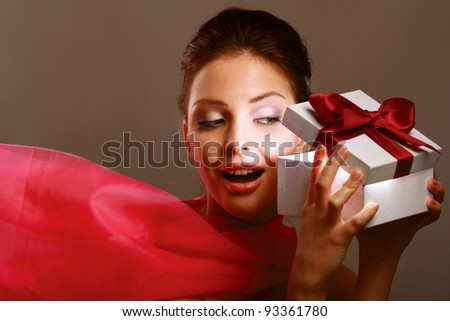 Young girl opening x-mass present isolated on grey background - stock photo