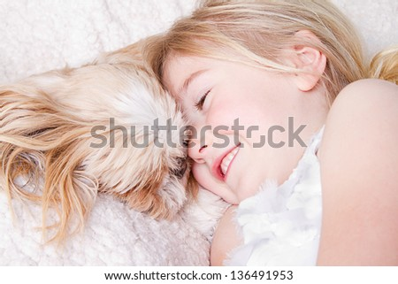 Young girl or child laying with a shih tzu dog - stock photo