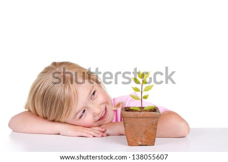 Young girl or child with a potted plant while smiling, isolated on white. - stock photo