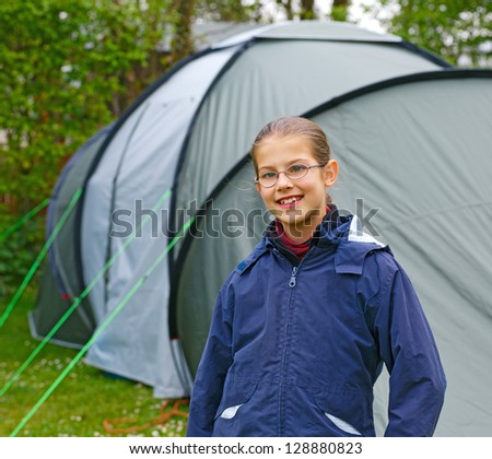 Young girl out camping learning how to pitch tent - stock photo