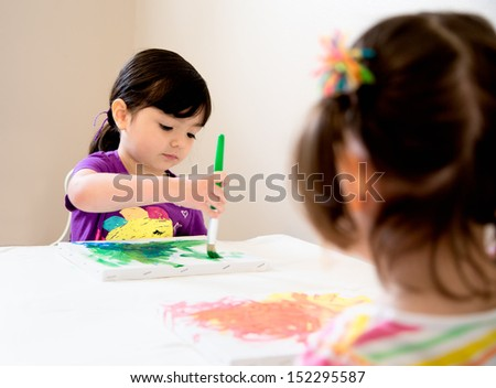 Young girl painting a picture as her sister watches - stock photo