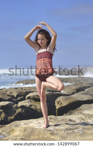 Young girl performs Vrksasana yoga tree pose on beautiful rocky beach in La Jolla, California - stock photo