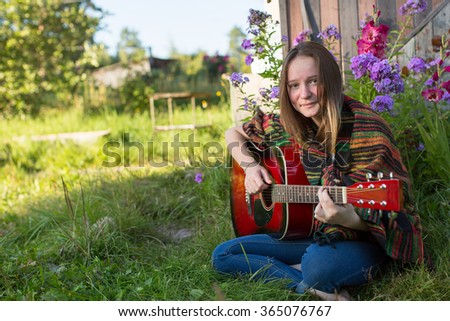 Young girl playing acoustic guitar, outdoors. - stock photo