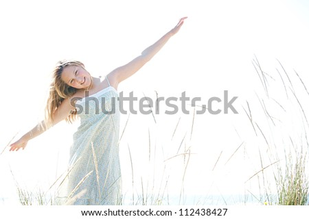 Young girl playing airplanes with her arms open against the sky, smiling. - stock photo