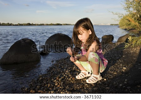 Young Girl Playing by the Columbia River in the Evening Sun - stock photo