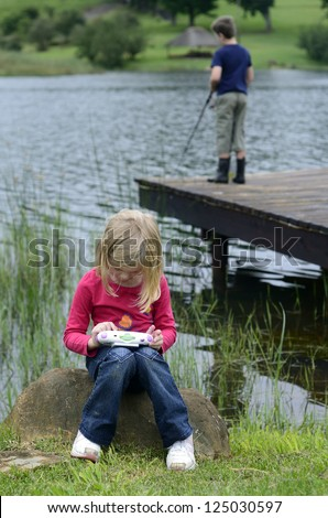 Young girl playing computer game in nature - stock photo