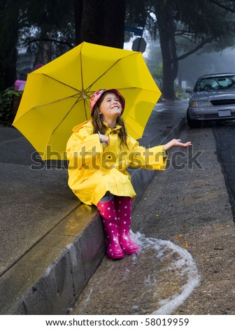 Young girl playing in rain 3 - stock photo