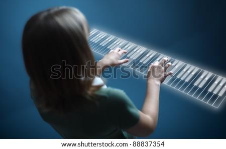 Young girl playing music on virtual piano keyboard - stock photo