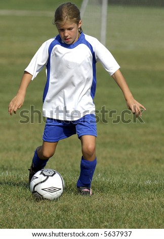 Young girl playing soccer - stock photo