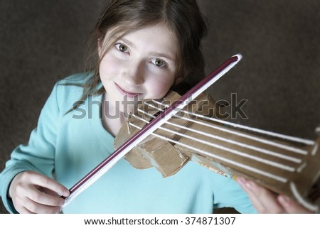 Young girl playing toy violin smiling happy - stock photo