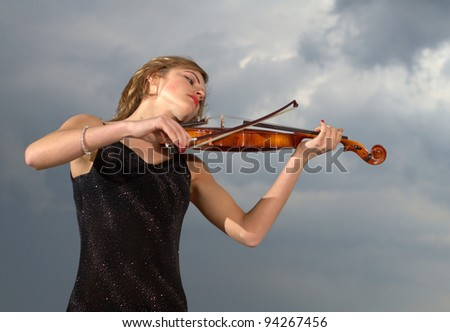 Young girl playing violin over blue sky and cloud - stock photo