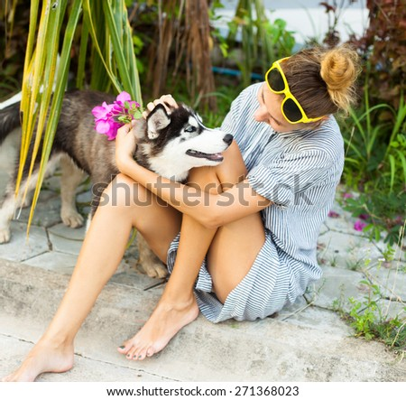 Young girl playing with her dog on the beach.Wear beautiful yellow shirt on white skirt enjoy her time.having fun.  - stock photo