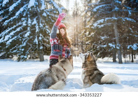 Young girl playing with the dog malamute in the winter - stock photo