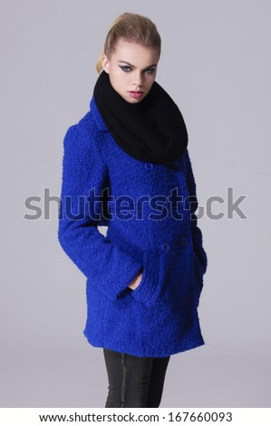 young girl posing over gray , model in a blue coat posing - stock photo