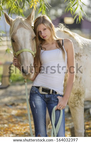 Young girl posing with her horse in white t-shirt and jeans - stock photo