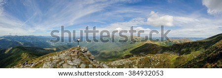 young girl practices yoga on a mountain top in the mountains - stock photo